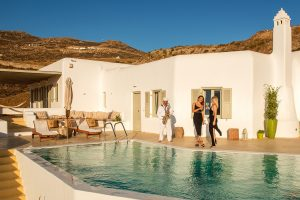 Two ladies talking by the pool of the Ftelia luxury villa rental in Mykonos. A sax player is playing