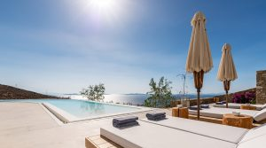 A Just White luxury villa swimming pool with sunbeds and a sea view of the Aegean.